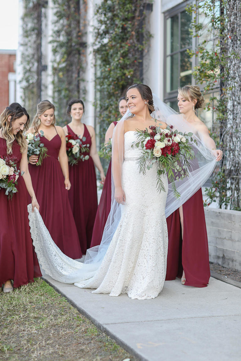Bride in Strapless Lace and Fitted Wedding Dress with Rhinestone Belt and Cathedral Length Veil and Bridesmaids in Long Burgundy Wine Red Dresses Holding Garden Style Red, Ivory, and Greenery Floral Bouquets | Tampa Bay Wedding Photographer Lifelong Photography Studios | Tampa Bay Wedding Planner Breezin' Weddings | Tampa Bay Wedding Hair and Makeup Team Michele Renee the Studio
