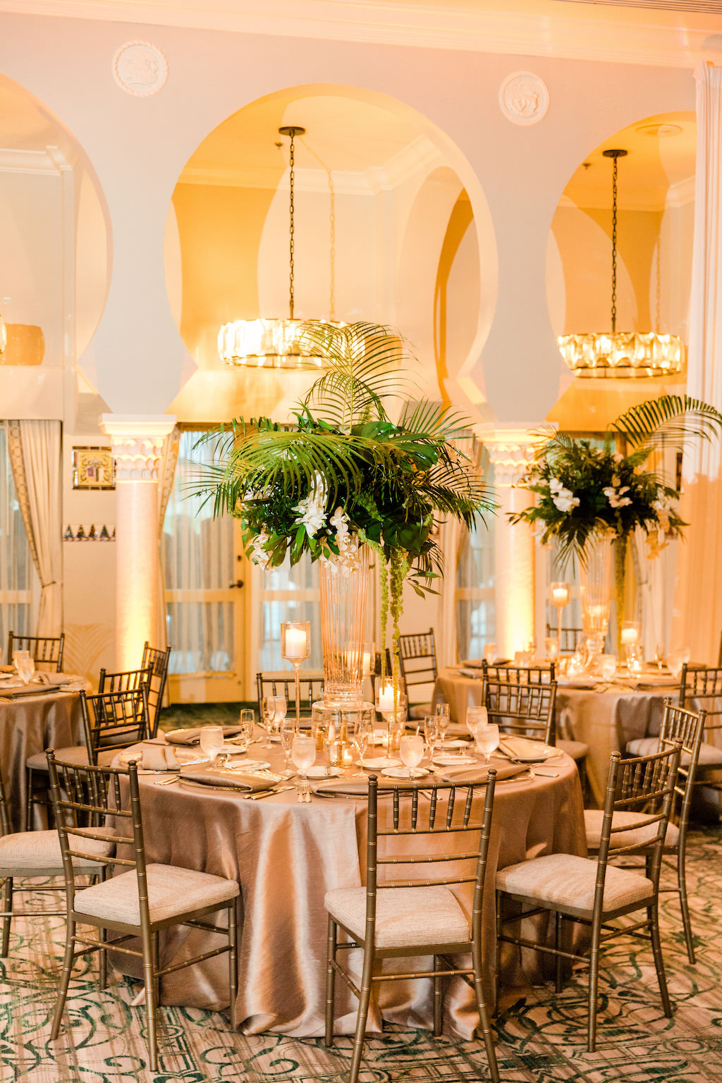 Tropical Inspired, Modern Wedding Reception Decor, Tall Centerpieces with Green Monstera Leaves, Large Palm Fronds, White Orchid Flowers, Round Tables with Silver Linens, Chiavari Chairs | Grand Ballroom of The Vinoy Renaissance St. Petersburg Resort & Golf Club | Over the Top Rental Linens | Tampa Bay Florist Bruce Wayne Florals | Florida Luxury Wedding Planner Parties A'La Carte