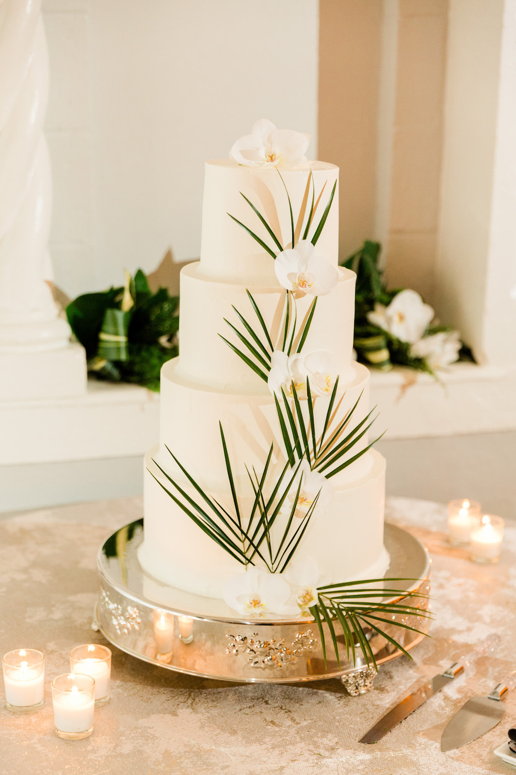 Modern, Smooth White Four Tier Wedding Cake with Dark Green Palm Leaves, White Orchid Flower, Silver Cake Stand | The Vinoy Renaissance St. Petersburg Resort & Golf Club | Luxury Florida Wedding Planner Parties A'La Carte
