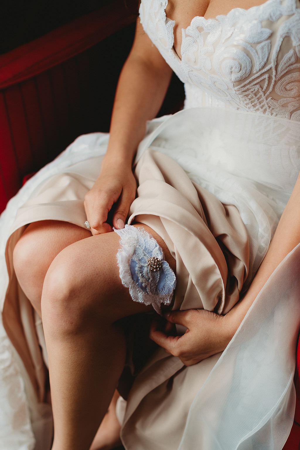 Bride Putting on Something Blue Lace Wedding Garter Portrait