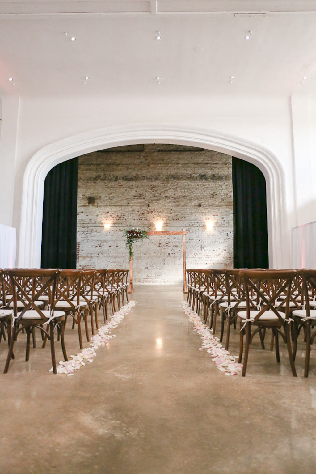 Industrial Elegant Wedding Ceremony Decor, White Brick Wall Backdrop, Wooden Chiavari Chairs, Blush Floral Petal Aisle, Wooden Arch with Greenery Accent | Tampa Wedding Photographer Lifelong Photography Studios | Tampa Wedding Planner Breezin' Weddings | Tampa Bay Wedding Venue Rialto Theatre