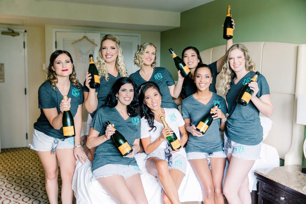 Modern, Florida Bride and Bridesmaid Getting Ready Group Photo on Bridal Suite Bed, Bottles of Champagne, Bridal Party in Matching Customized Monogram Shirts | Tampa Bay Wedding Hair and Makeup Artist Michele Renee The Studio | Florida Waterfront Resort Wedding Venue The Vinoy Renaissance St. Petersburg Resort & Golf Club