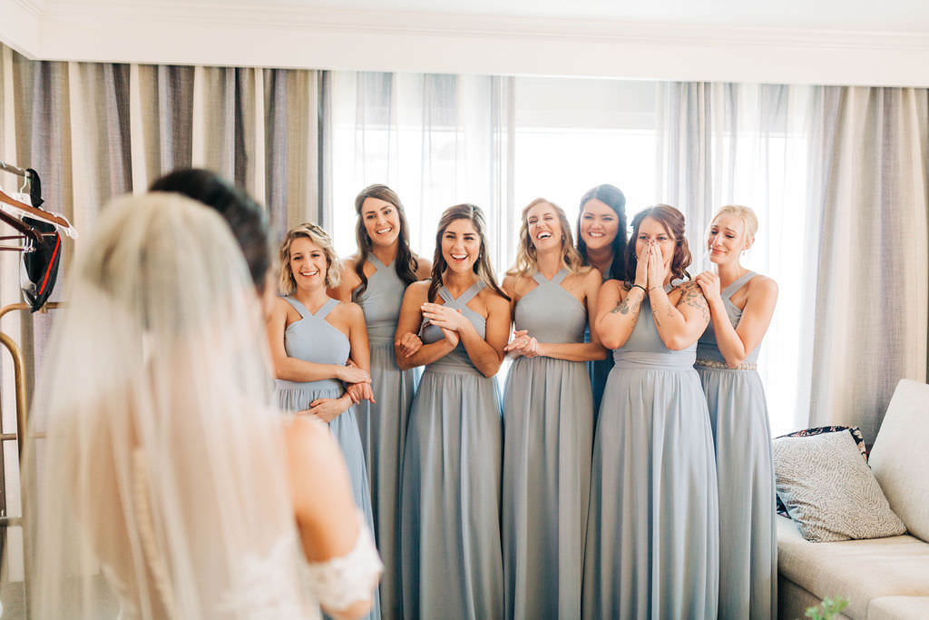 Bridesmaids in Matching Cross Halter Long Dusty Blue Dresses First Reaction Wedding Portrait to Seeing Bride