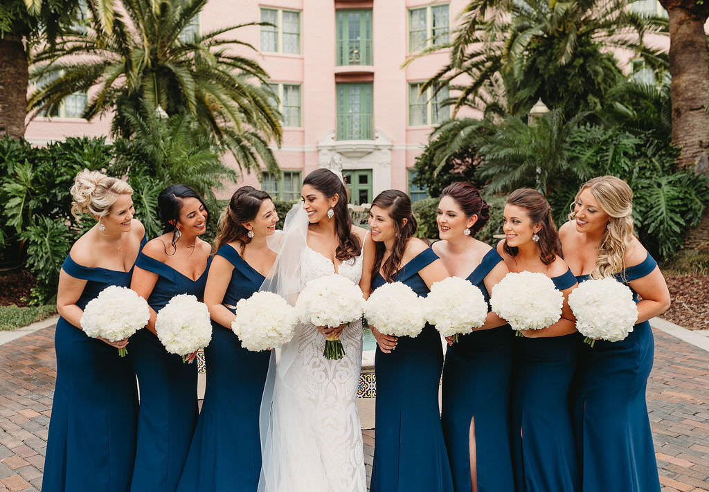 Tampa Bay Bride and Bridesmaids Wedding Portrait, Bridesmaids in Matching Classic Blue Off the Shoulder Long Fitted Dresses, Bride in Fit and Flare Lace Spaghetti Strap Plunging Sweetheart Neckline Hayley Paige Wedding Dress with Round Traditional White Floral Bouquets | St. Pete Wedding Venue The Vinoy
