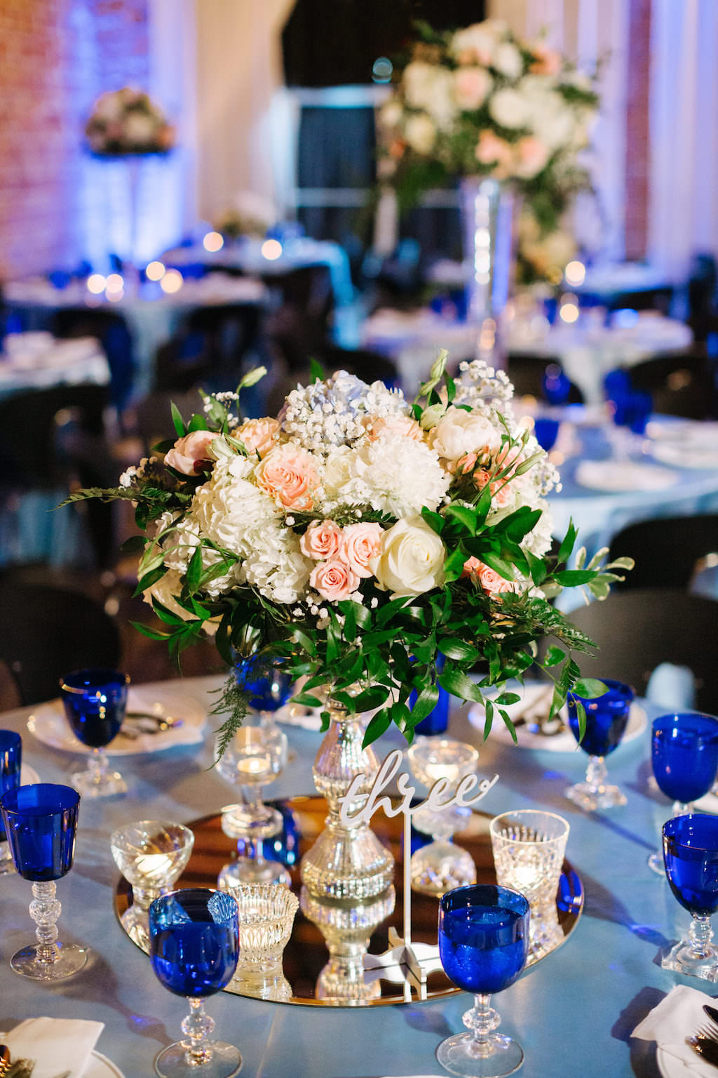 Modern, Romantic Reception and Wedding Decor, Low Floral Centerpieces with White, Peach, Pink, Ivory Flowers, Round Tables with Silver Tablecloths, Blue Stemware | Tampa Bay Premier Wedding Venue NOVA 535 in Downtown St. Pete