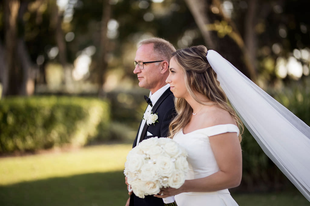 Classic, Formal Bride and Father Walking Down the Wedding Ceremony Aisle Processional in White Off the Shoulder Wedding Dress, Cathedral Length Veil and Round White, Ivory Rose Floral Bouquet