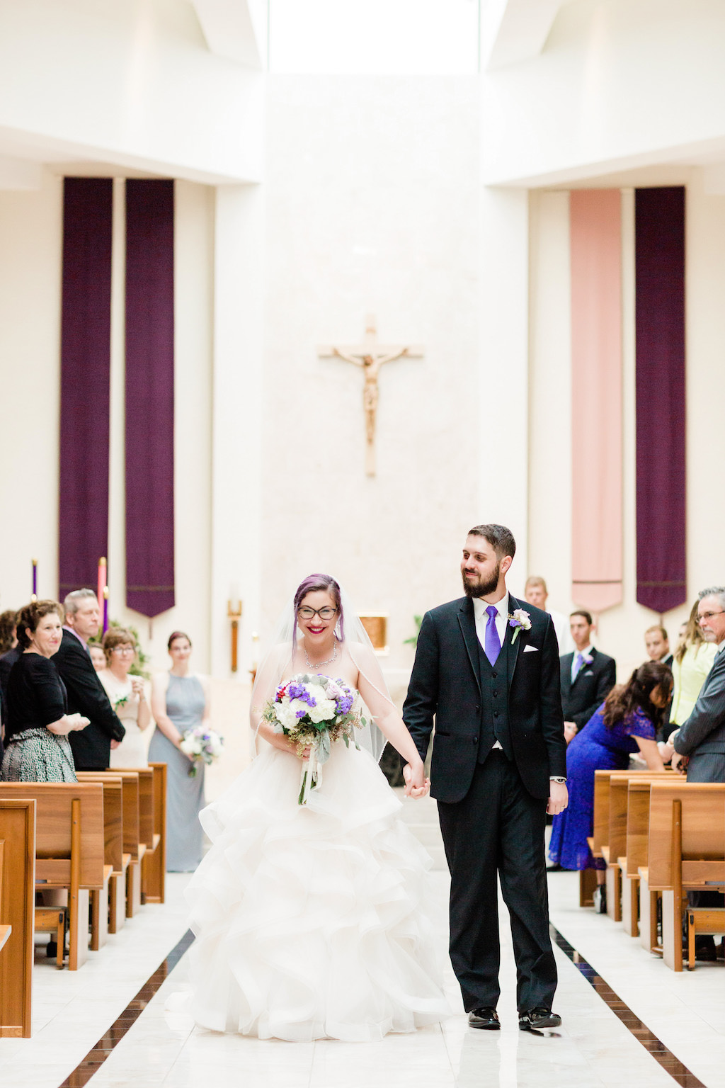 Modern, Unique Florida Bride and Groom Just Married in Wedding Recessional, Wearing Ballgown Wedding Dress, Holding Purple and Ivory Floral Bouquet, Traditional Catholic Wedding Ceremony