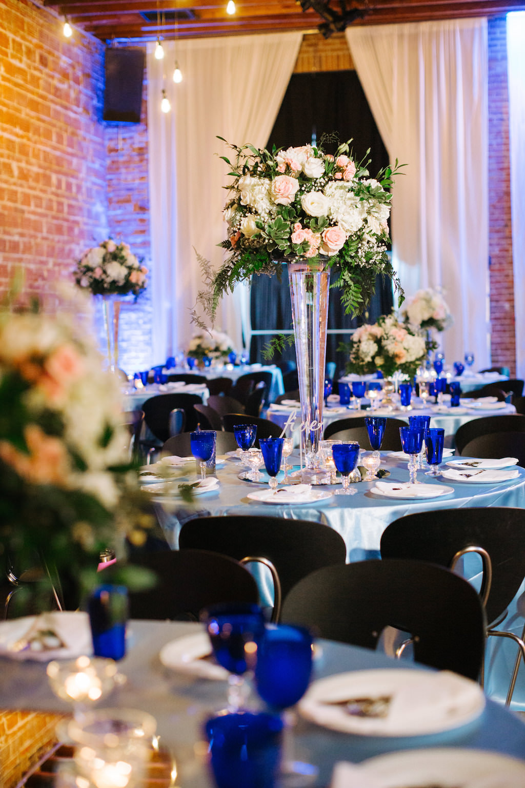 Modern, Romantic Reception Wedding Decor, Tall Floral Centerpieces with White, Peach, Pink, Ivory Flowers, Round Tables with Silver Tablecloths, Blue Stemware | Tampa Bay Premier Wedding Venue NOVA 535 in Downtown St. Pete