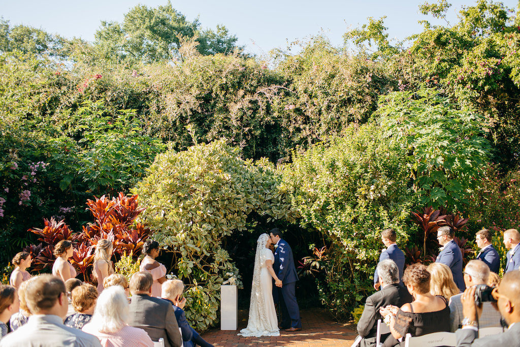 Florida Bride and Groom Exchanging First Kiss Garden Wedding Ceremony Portrait | Outdoor Tropical Inspired St. Pete Wedding Venue | Sunken Gardens