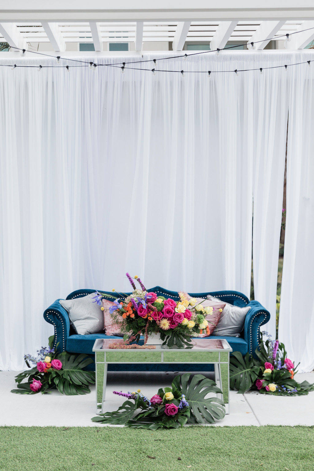 Modern, Tropical Garden Inspired Wedding Decor, Blue Velvet Lounge Seating and Couch, Dusty Rose Gold and Silver Accent Pillows, Mirrored Table, Whimsical Pink, Yellow, Orange, Purple Floral Centerpiece with Green Monstera Leaves, Against White Draping with Romantic Outdoor String Lighting   Tampa Bay Wedding Planner Special Moments Event Planning   Tampa Bay Wedding Florist Gabro Event Services