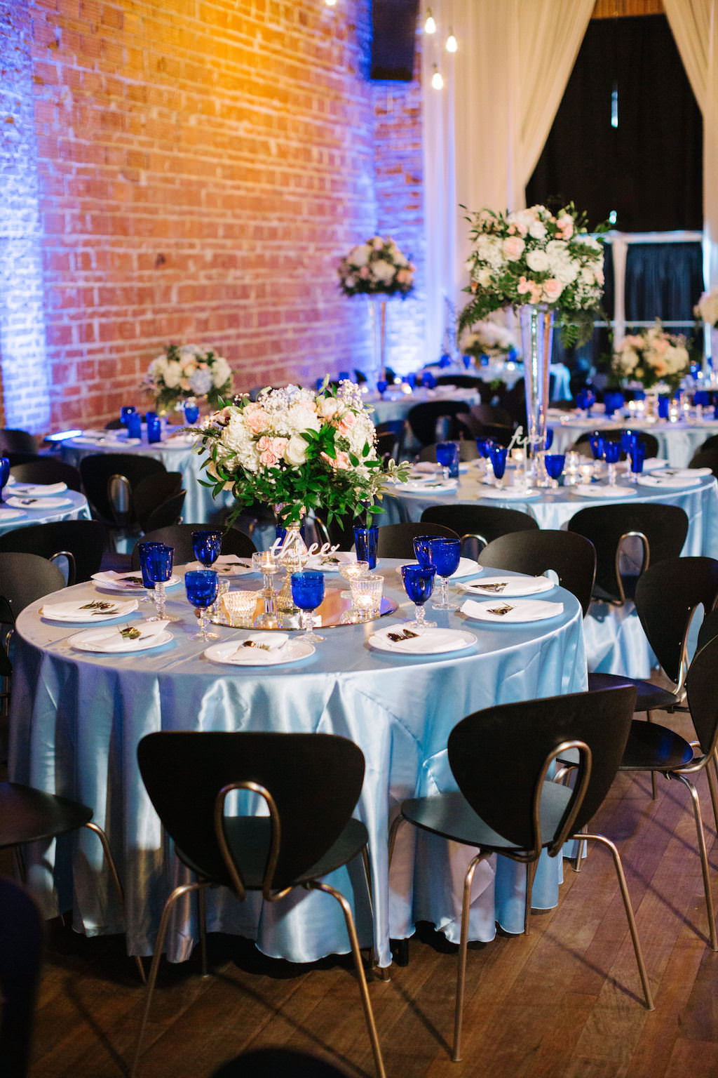 Modern, Romantic Reception and Wedding Decor, Low Floral Centerpieces with White, Peach, Pink, Ivory Flowers, Round Tables with Silver Tablecloths, Blue Stemware | Tampa Bay Historic Wedding Venue NOVA 535 in Downtown St. Pete