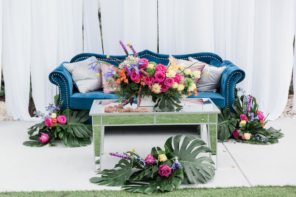 Modern, Tropical Garden Inspired Wedding Decor, Blue Velvet Lounge Seating and Couch, Dusty Rose Gold and Silver Accent Pillows, Mirrored Table, Whimsical Pink, Yellow, Orange, Purple Floral Centerpiece with Green Monstera Leaves, Against White Draping   Tampa Bay Wedding Planner Special Moments Event Planning   Tampa Bay Wedding Florist Gabro Event Services