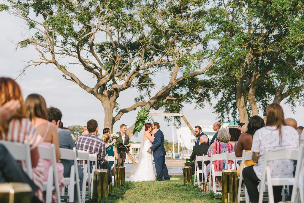 Florida Bride and Groom Exchanging First Kiss During Wedding Ceremony Under Modern Unique Wooden Geometric Ceremony Arch with Tropical Monstera Palm Leaves   Wedding Photographer Kera Photography   St. Petersburg Outdoor Waterfront Wedding Venue The Poynter Institute