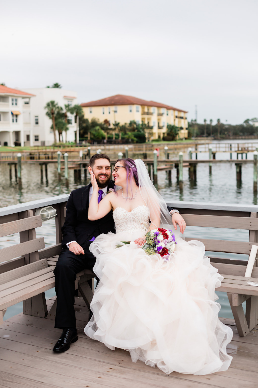 Modern, Romantic Florida Bride in Ballgown Wedding Dress, Unique Wedding Style with Purple Hair and Glasses, Holding Whimsical Bridal Bouquet, Purple, Ivory, White, Red, Flowers with Greenery | Tampa Bay Waterfront Wedding Venue Beso Del Sol