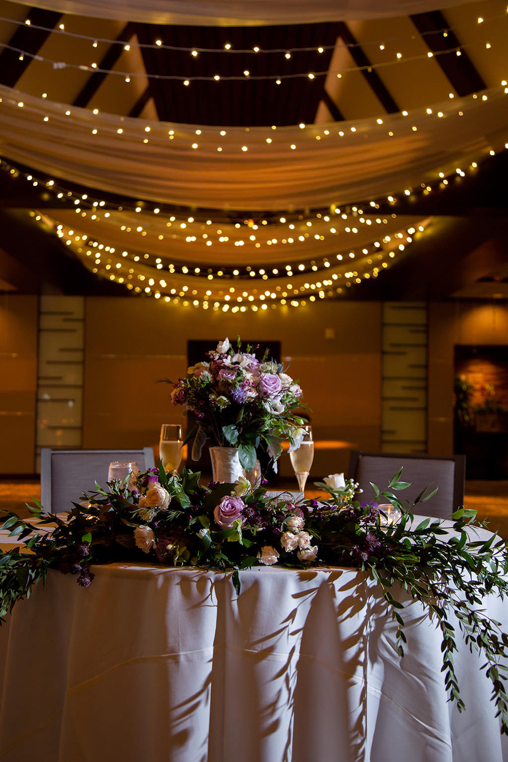 Elegant, Classic Vintage Garden Inspired Wedding Reception Decor and Sweetheart Table, Lush Cascading Centerpiece, Purple, Lilac Roses, Green Hydrangeas, Blush Pink and Greenery Floral Arrangement, White Ceiling Draping with String Lights | Sarasota Wedding Planner Laura Detwiler Events | Wedding Venue Marie Selby Botanical Gardens