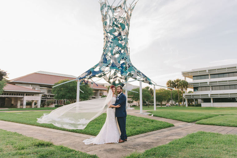 Creative Florida Bride and Groom Wedding Portrait with Bride's Cathedral Length Veil Blowing in Wind Outside with Art Sculpture | Wedding Photographer Kera Photography | St. Pete Wedding Venue The Poynter Institute