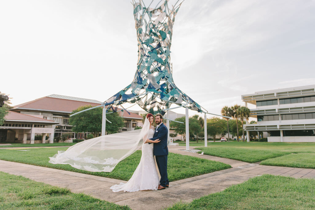 Creative Florida Bride and Groom Wedding Portrait with Bride's Cathedral Length Veil Blowing in Wind Outside with Art Sculpture   Wedding Photographer Kera Photography   St. Pete Wedding Venue The Poynter Institute