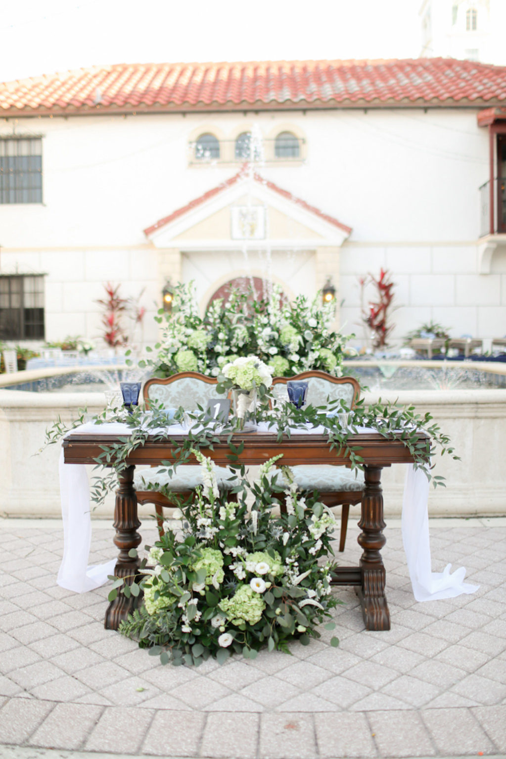 Rustic Elegant Wedding Reception Decor, Wooden Sweetheart Table with White Table Runner, Greenery, White, Ivory Floral Arrangements and Centerpiece | Wedding Photographer Lifelong Photography Studios | Wedding Venue Bishop Museum of Science and Nature | Sarasota Wedding Planner Kelly Kennedy Weddings and Events