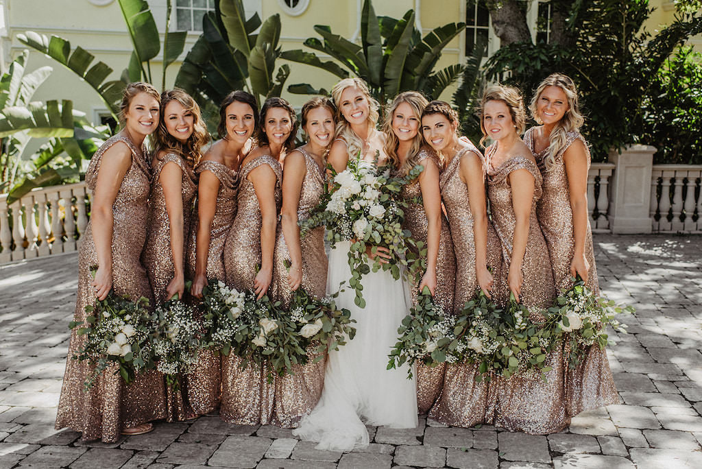 Outdoor Bride and Bridesmaids Courtyard Wedding Photo, Bridesmaids in Matching Gold Glitter Sequin Sparkly Scoop Neck Dresses, Bride in Spaghetti Strap Lace Bodice and Tulle Skirt with Organic Greenery and White Ivory Floral Bouquets Wedding Dress | Tampa Bay Wedding Hair and Makeup Femme Akoi