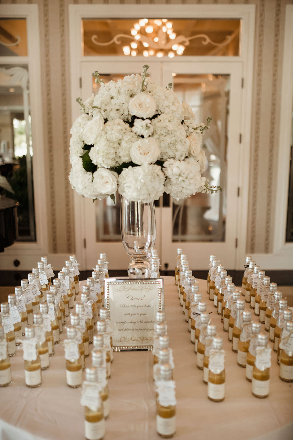 Classic, Formal Wedding Reception Welcome Table, Tall Glass Vase with White, Ivory, Hydrangeas, Roses Floral Arrangement, Personalized Champagne Bottle Seating Cards