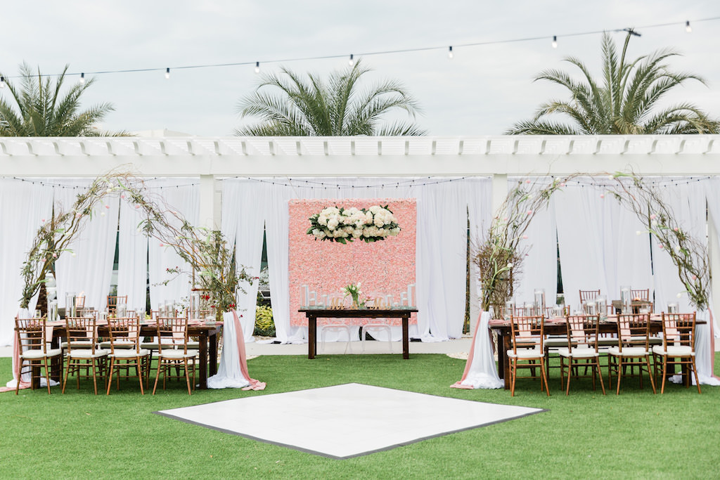 Modern, Whimsical Garden Wedding Decor and Reception under Gazebo, Pink Floral Boxwood Wall, White Draping, Hanging Floral Arrangement, Long Feasting Tables. Rose Gold Chiavari Chairs, Feasting Tables, Arching Thistle and Stems Arrangement, Sweetheart Table with Ghost Acrylic Chairs, Outdoor Dance floor   Tampa Bay Wedding Planner Special Moments Event Planning   Tampa Bay Wedding Florist Gabro Event Services   Tampa Bay Wedding Rentals A Chair Affair
