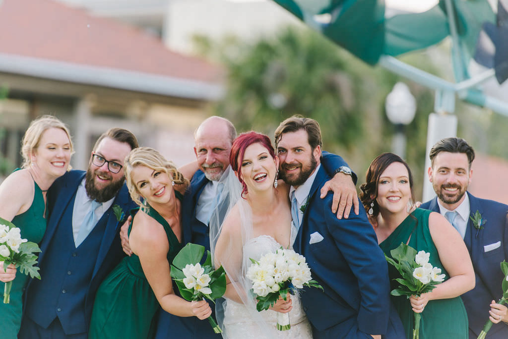 Florida Bride, Groom, Bridesmaid in Emerald Green Dresses Holding White Tulip Floral Bouquets, Groomsmen in Blue Suits   St. Pete Wedding Photographer Kera Photography   Tampa Bay Wedding Hair and Makeup Artist Destiny and Light Hair and Makeup