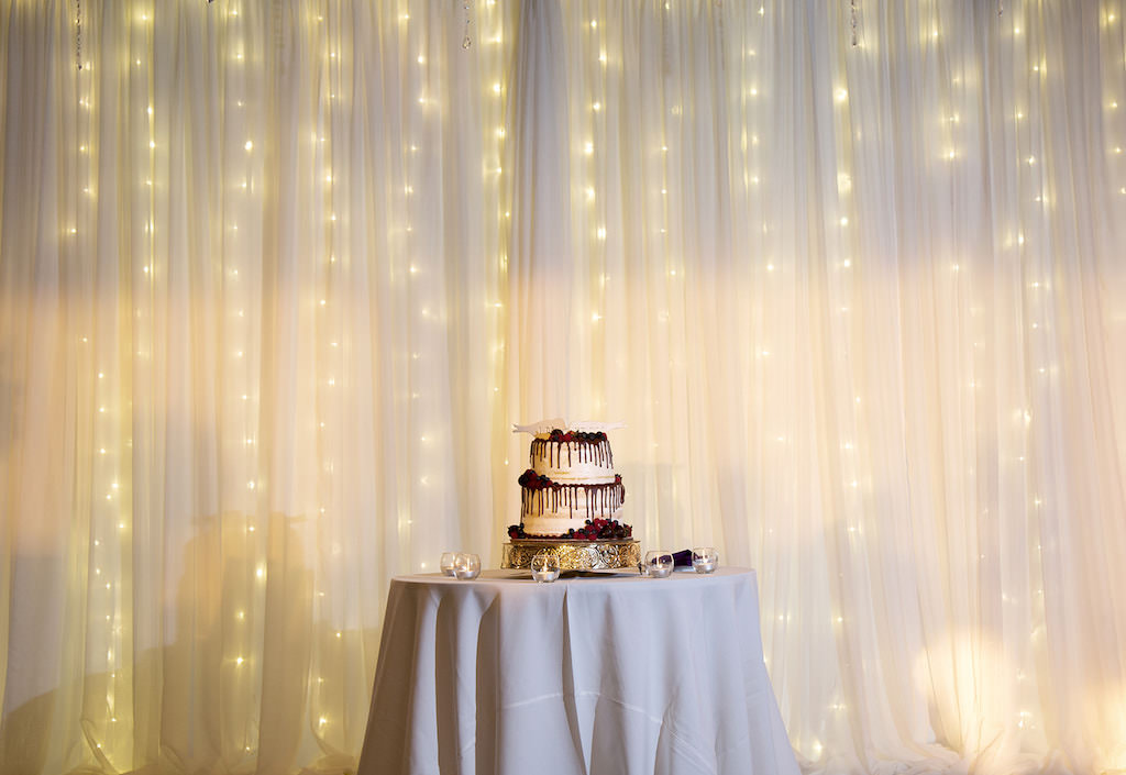 Elegant Two Tier White Wedding Cake, Chocolate Drip Frosting, Berries, White Lovebirds Cake Topper, White Draping with Romantic String Lighting Backdrop | Tampa Wedding Planner Laura Detwiler Events