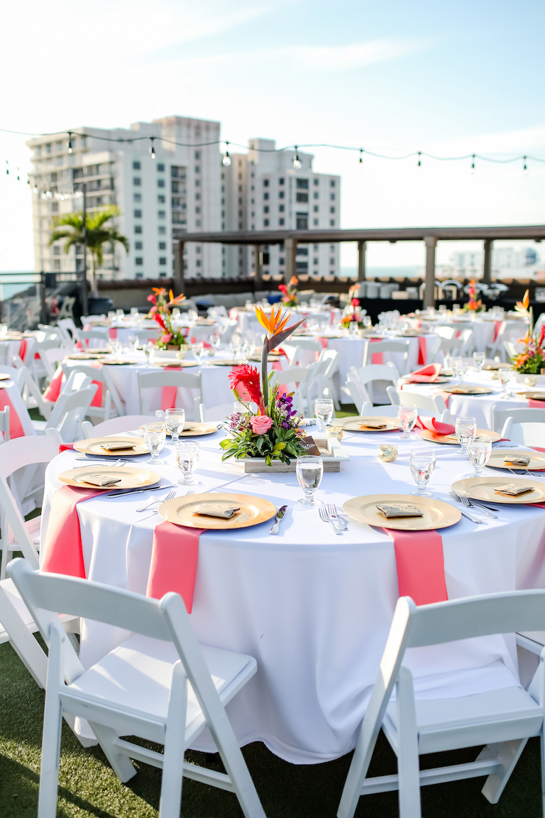 Tropical, Florida Beach Inspired Wedding Decor at Rooftop Waterfront Wedding Reception, Round Tables with White Tablecloth, Low Floral Centerpieces, Vibrant Orange, Pink, Coral, Yellow Flowers, and Greenery, Gold Accents, String Lighting | St. Pete Beach Wedding Venue Hotel Zamora | Tampa Bay Wedding Photographer Lifelong Photography Studios | Tampa Wedding Rentals Gabro Event Services