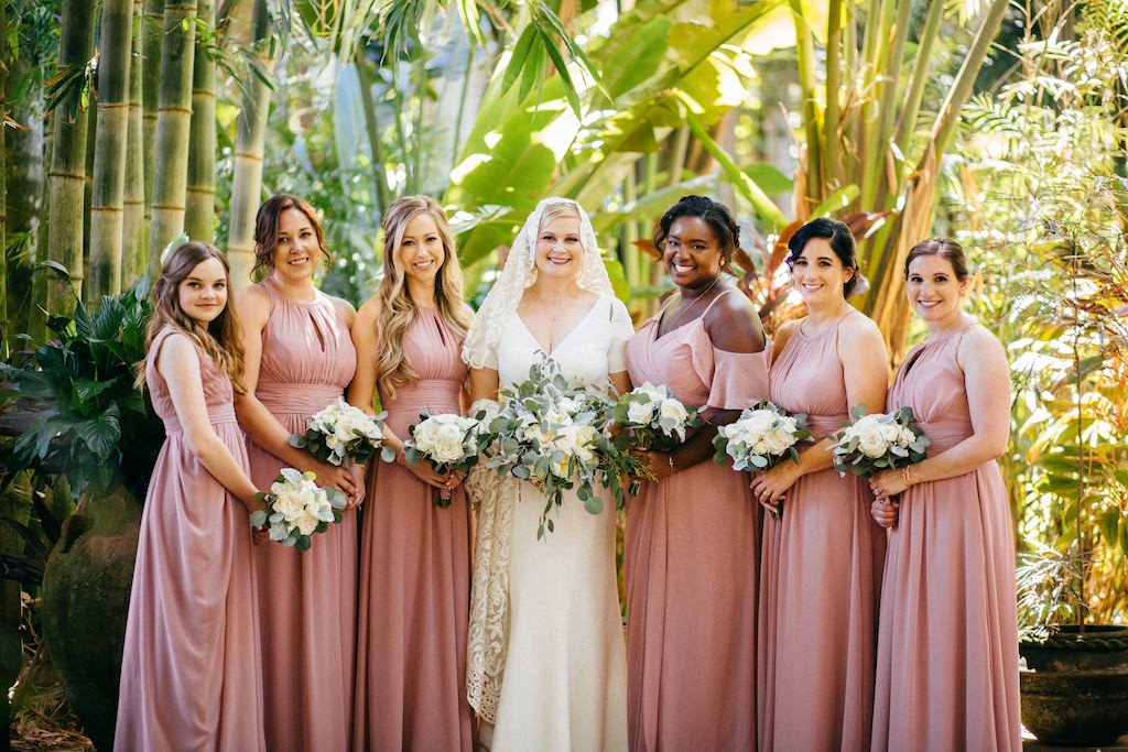 Tampa Bay Bride in V Neckline Simple Classic with Sleeves Wedding Dress and Lace Veil Holding Organic Greenery and Ivory Floral Bouquet, Bridesmaids in Mauve Pink Dresses Holding White Flower Bouquets | Tampa Bay Wedding Hair and Makeup Femme Akoi