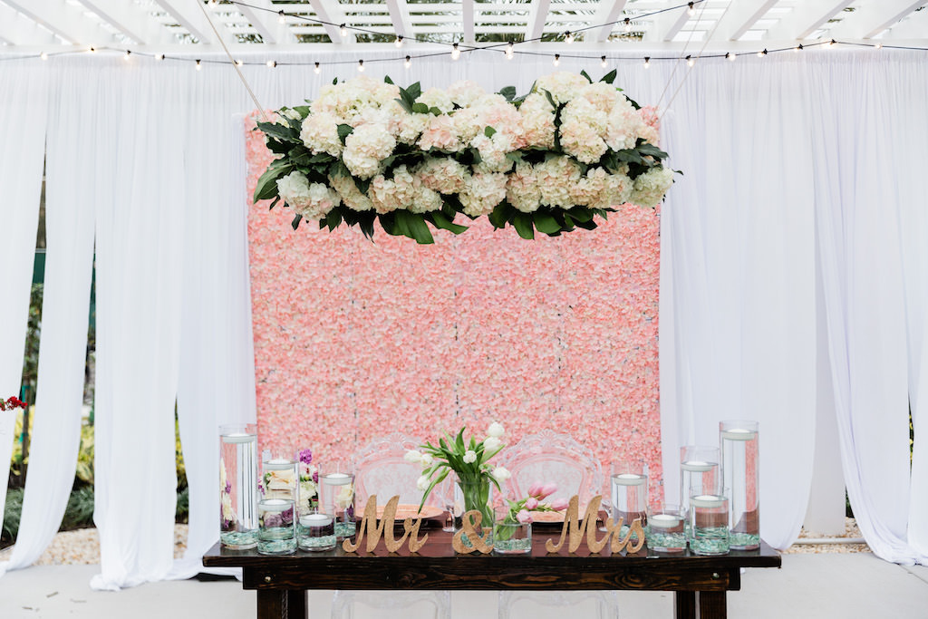 Modern, Whimsical Garden Wedding Decor and Sweetheart Table, Pink Floral Boxwood Wall, White Draping, Ivory, Blush Pink Hanging Floral Arrangement with Greenery, Clear Floating Candles, Gold Mr. and Mrs. Tabletop, White Lilly Bouquet, Sweetheart Table with Ghost Acrylic Chairs, Outdoor Dance floor   Tampa Bay Wedding Planner Special Moments Event Planning   Tampa Bay Wedding Florist Gabro Event Services   Tampa Bay Wedding Rentals A Chair Affair