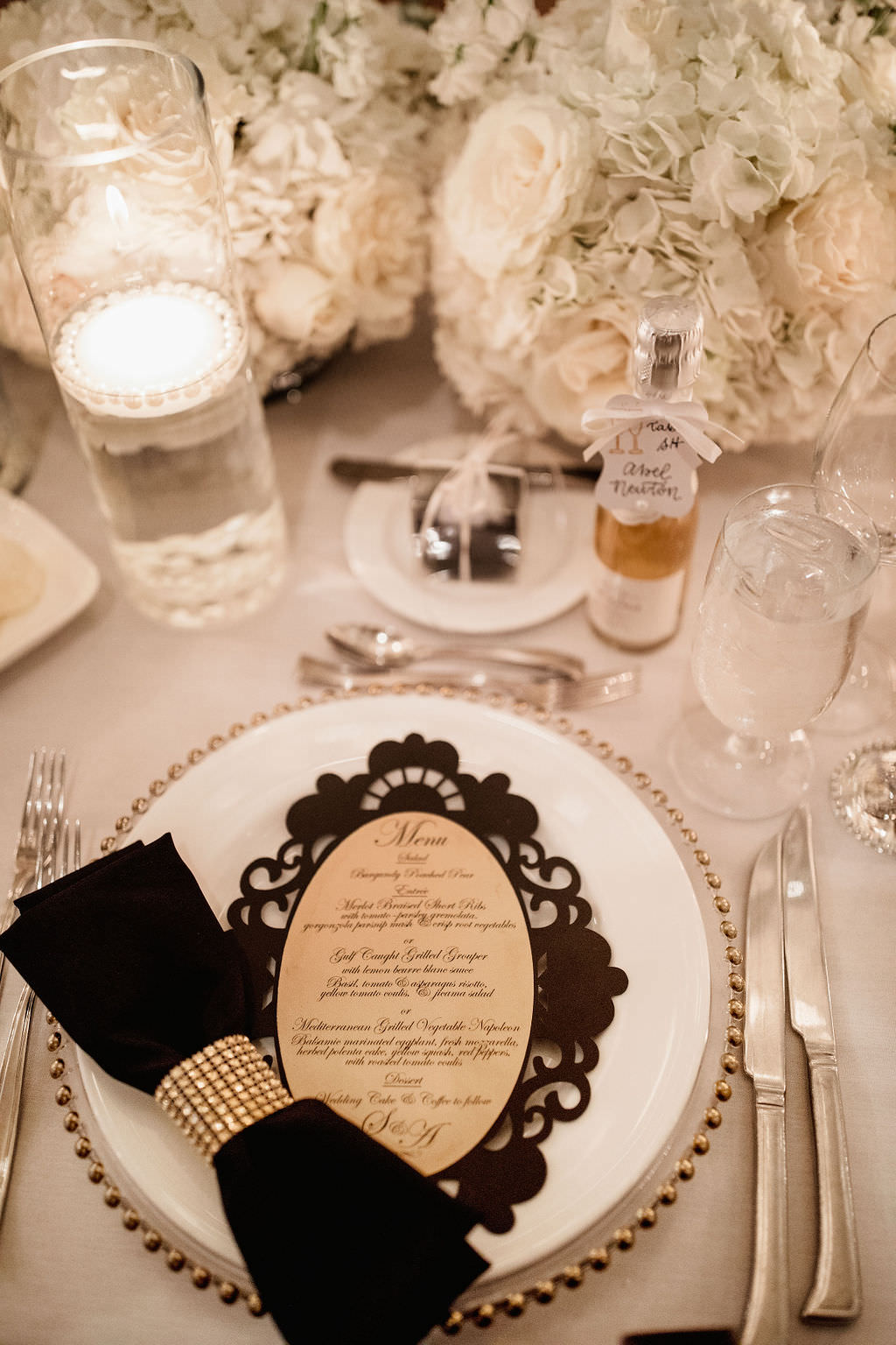 Classic Formal Wedding Reception Decor, Black Linen with Rhinestone Napkin Ring, Clear Glass and Gold Beaded Rim Charger, White, Ivory Floral Centerpiece, Floating Candle in Hurricane Glass Vase, Custom Lace Style Menu Stationery