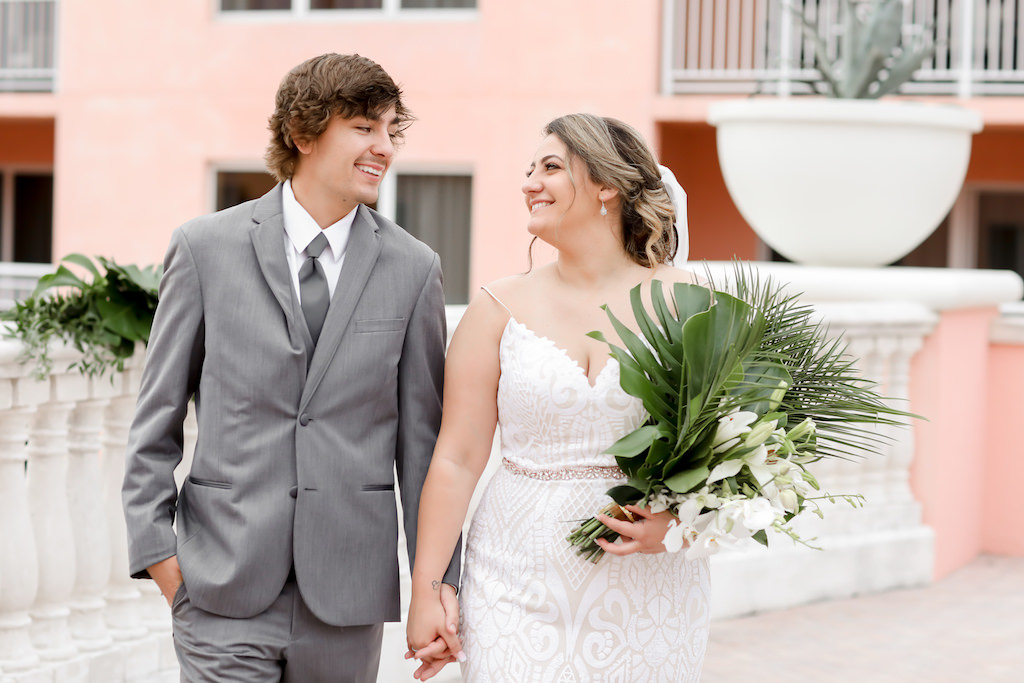 Clearwater Beach Bride and Groom Holding Hands, Bride in Spaghetti Strap Lace Fitted V Neckline Wedding Dress with Rhinestone Belt Holding Tropical Monstera Leaf, Areca Palm Leaves and White Orchid Floral Bouquet, Groom in Grey Suit   Tampa Bay Wedding Photographer Lifelong Photography Studios