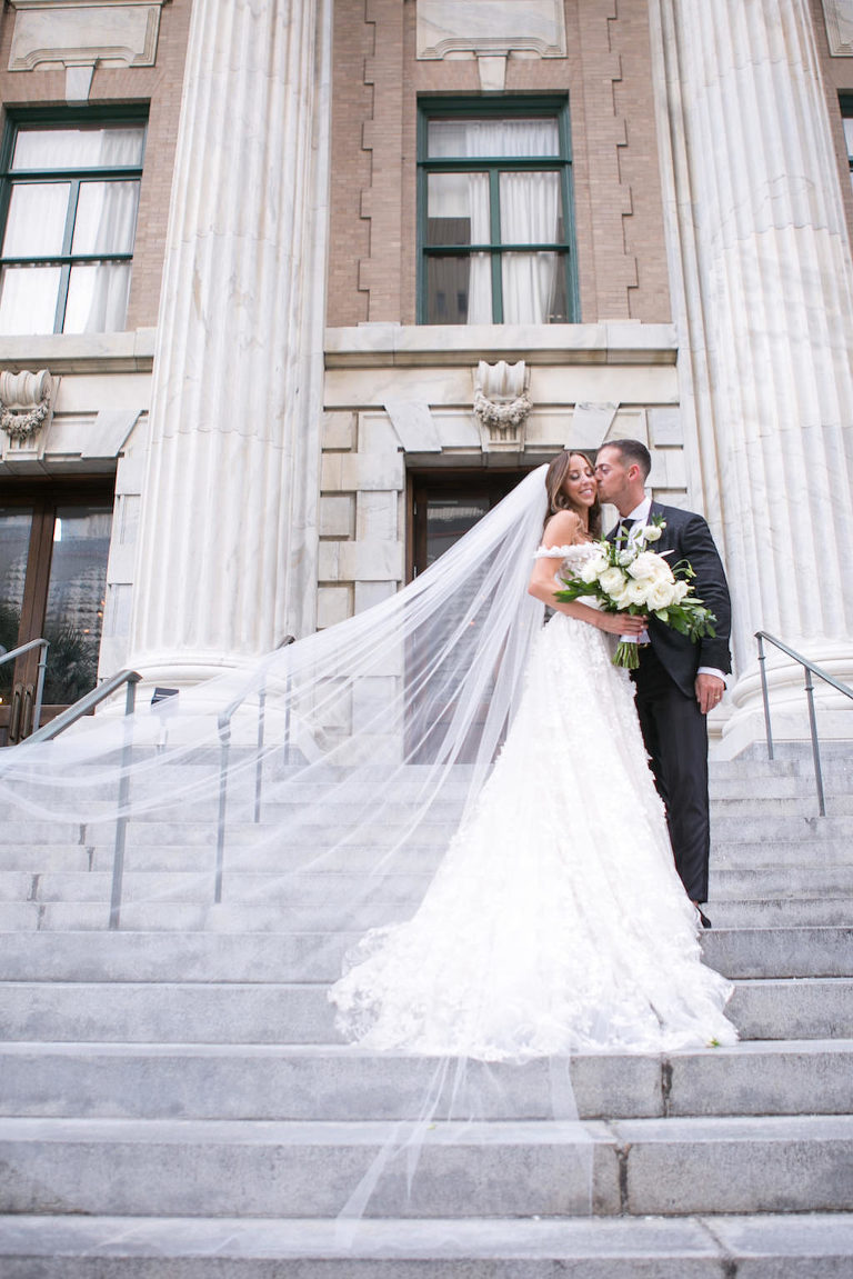 Elegant Florida Bride and Groom Wedding Portrait on Steps of Downtown Tampa Hotel Venue Le Meridien and Veil Blowing in Wind | Tampa Bay Wedding Photographer Carrie Wildes Photography | Tampa Dress Shop Isabel O'Neil Bridal Collection