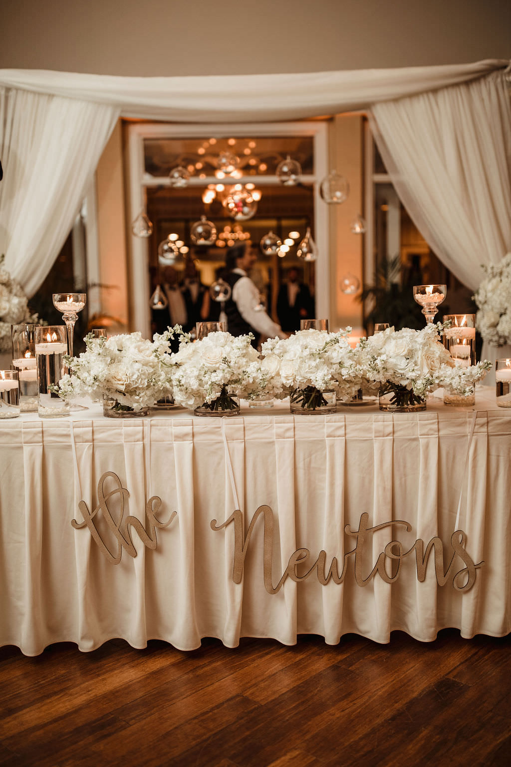 Classic, Formal Wedding Reception Decor, Sweetheart Table with Ivory Linen, Custom Laser Cut Name Sign, White Floral Arrangement Centerpieces and Floating Candles