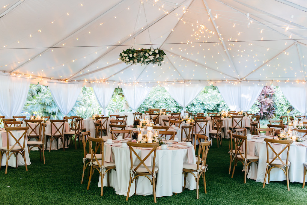 Elegant, Simple, Classic Outdoor Florida Garden Tent Wedding Reception | Outdoor Tent Wedding Reception Decor with Hanging Greenery and White Ivory Floral Wreath, String Lights, Round Tables with White Linens, Wooden Crossback Chairs, Hurricane Glass Candlestick Centerpieces | Tampa Bay Wedding Rentals Gabro Event Services | Tampa Bay Wedding DJ Graingertainment