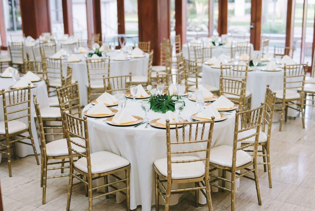 Modern Classic Tropical Wedding Reception Decor, Round Tables with White Linens, Gold Chiavari Chairs, Gold Chargers, Monstera Palm Tree Leaf Centerpiece   Wedding Photographer Kera Photography   St. Pete Wedding Venue The Poynter Institute