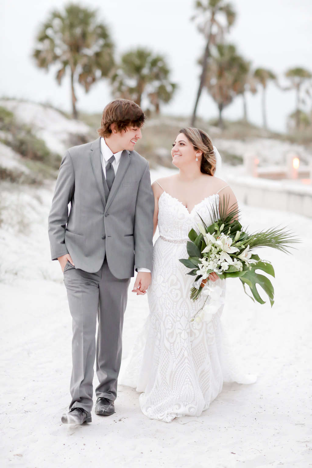 Clearwater Beach Bride and Groom Wedding Portrait, Bride in Fitted Spaghetti Strap Lace V Neckline Wedding Dress with Rhinestone Belt Holding Tropical Monstera Leaf, Areca Leaves and White Orchid Floral Bouquet   Tampa Bay Wedding Photographer Lifelong Photography Studios