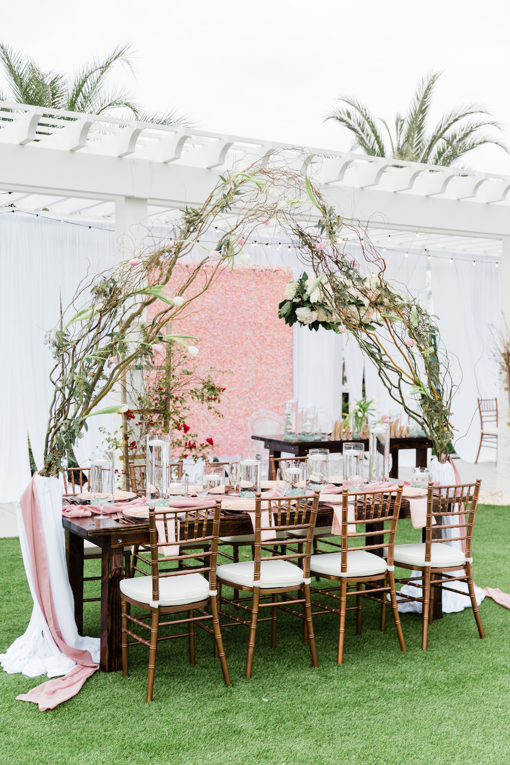 Modern Florida Bride Whimsical Garden Wedding Decor and Reception under Gazebo, Pink Floral Boxwood Wall, White Draping, Hanging Floral Arrangement, Long Feasting Tables. Rose Gold Chiavari Chairs, Floral Curly Willow Arches,   Tampa Bay Wedding Planner Special Moments Event Planning   Tampa Bay Wedding Florist Gabro Event Services   Tampa Bay Wedding Rentals A Chair Affair Wall, White Draping, Hanging Floral Arrangement, Long Feasting Tables. Rose Gold Chiavari Chairs, Floral Curly Willow Arches, Sweetheart Table with Ghost Acrylic Chairs, Outdoor Dance floor   Tampa Bay Wedding Planner Special Moments Event Planning   Tampa Bay Wedding Florist Gabro Event Services   Tampa Bay Wedding Rentals A Chair Affair   Tampa Bay Hair and Makeup Artists Femme Akoi   Tampa Bay Couture Wedding Dress Boutique Isabel O'Neil Bridal Collection  