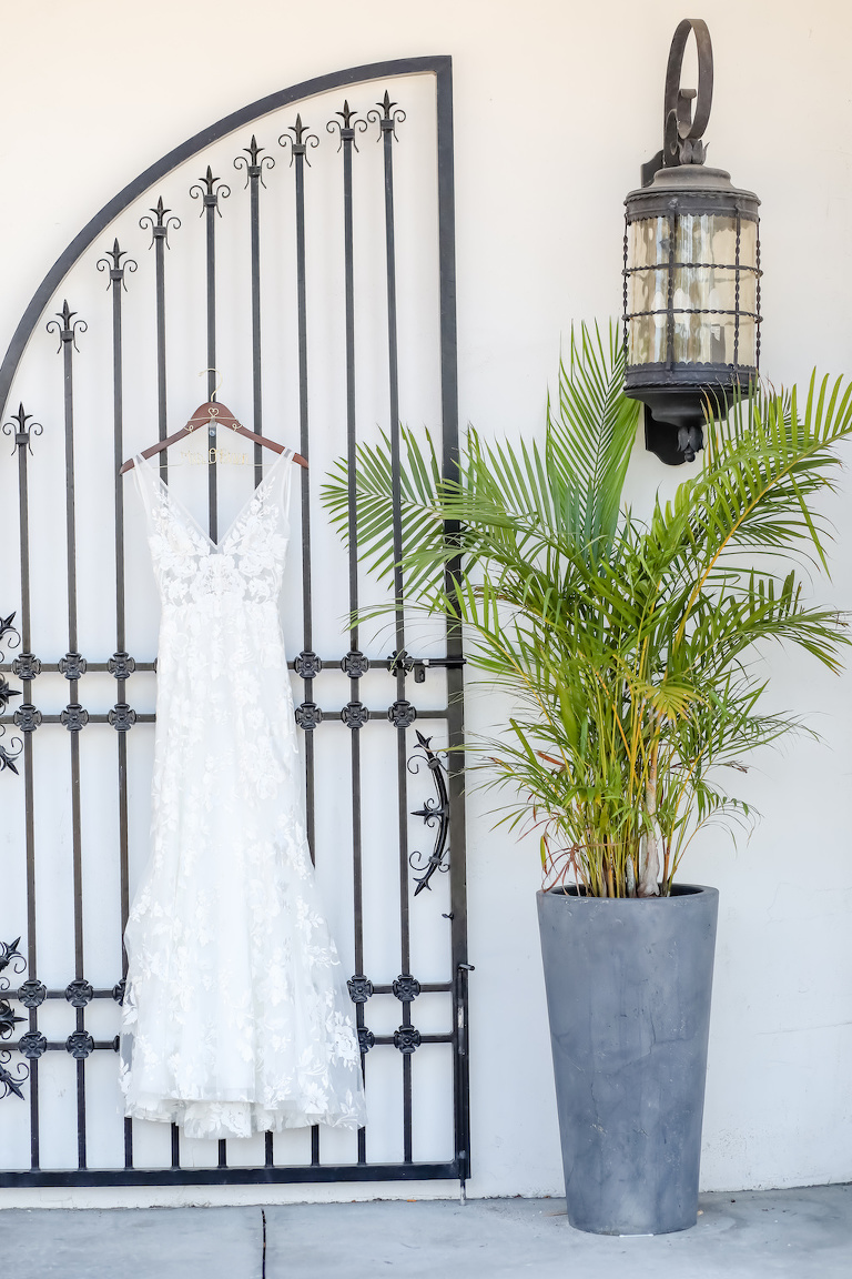 White Boho Wedding Dress By Made With Love Bridal Collection, Hanging on Iron Gate | St. Pete Beach Wedding Venue Hotel Zamora | Tampa Bay Wedding Photographer Lifelong Photography Studios