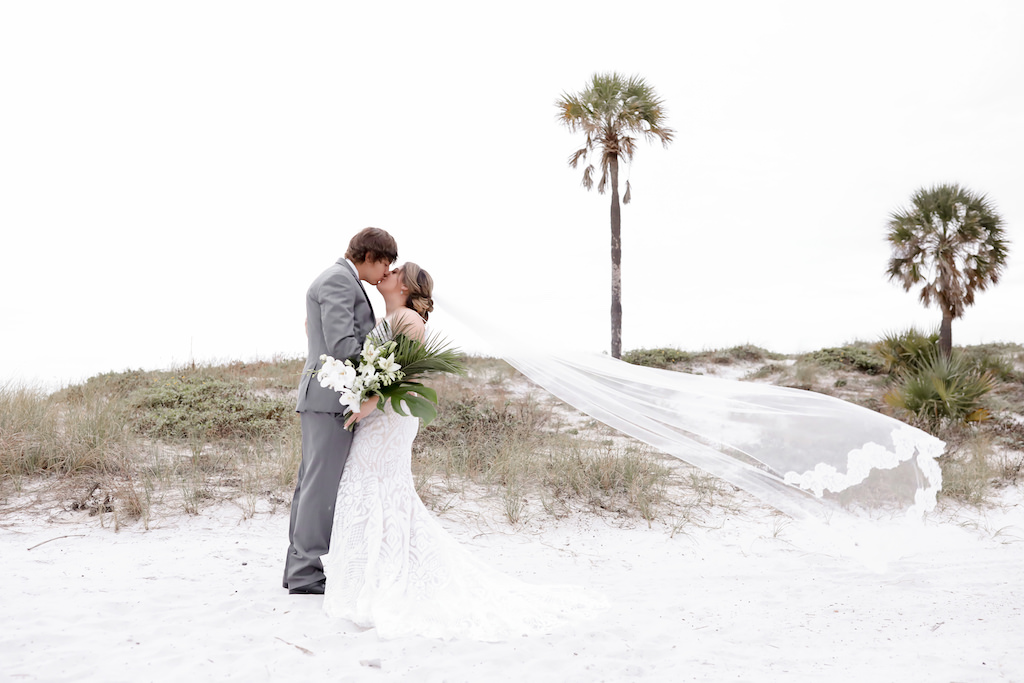 Clearwater Beach Bride and Groom Kissing with Cathedral Length Veil Blowing in Wind Creative Photo   Tampa Bay Wedding Photographer Lifelong Photography Studios