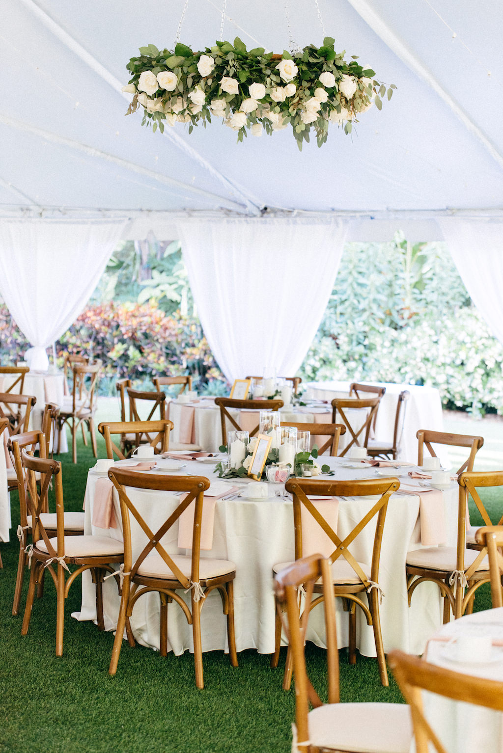 Elegant, Simple, Classic Garden Outdoor Tent Wedding Reception Decor, Hanging Greenery and White Ivory Floral Wreath, String Lights, Round Tables with White Linens, Wooden Crossback Chairs, Hurricane Glass Candlestick Centerpieces | Tampa Bay Wedding Rentals Gabro Event Services