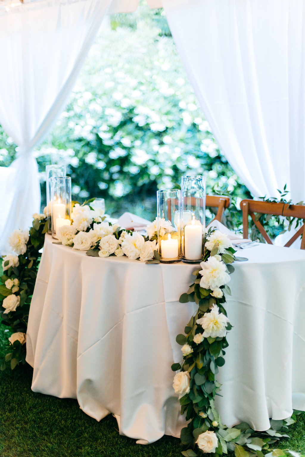 Elegant, Simple, Classic Garden Tent Wedding Reception Decor, Sweetheart Table with White Linen, Wooden Crossback Chairs, Greenery Garland with White and Ivory Florals, Hurricane Glass Candlesticks | Tampa Bay Wedding Rentals Gabro Event Services