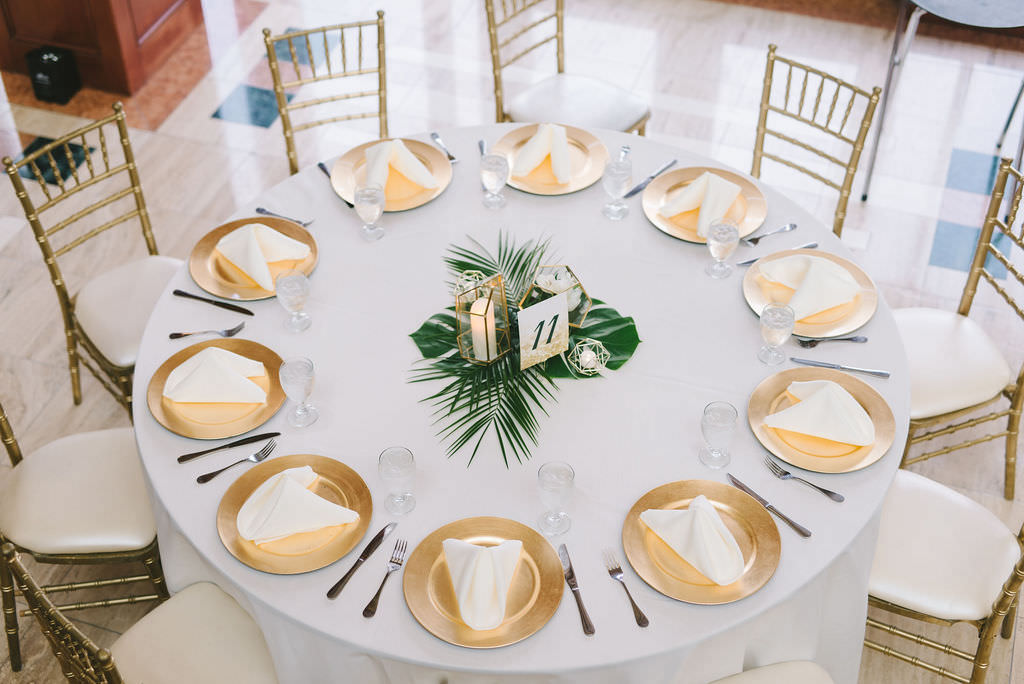 Modern Classic Tropical Wedding Reception Decor, Round Tables with White Linens, Gold Chiavari Chairs, Gold Chargers, Monstera Palm Tree Leaf Centerpiece and Geometric Candle Holders   Wedding Photographer Kera Photography   St. Pete Wedding Venue The Poynter Institute