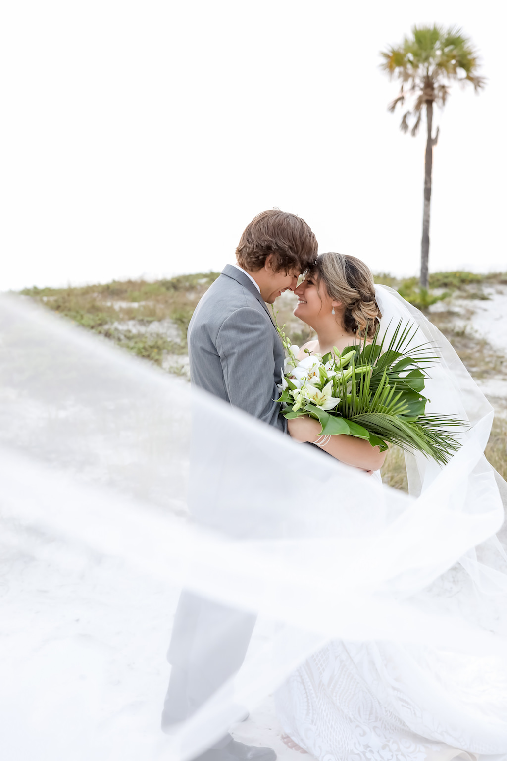 Clearwater Beach Bride and Groom Creative Photo with Cathedral Length Veil Blowing in Wind   Tampa Bay Wedding Photographer Lifelong Photography Studios