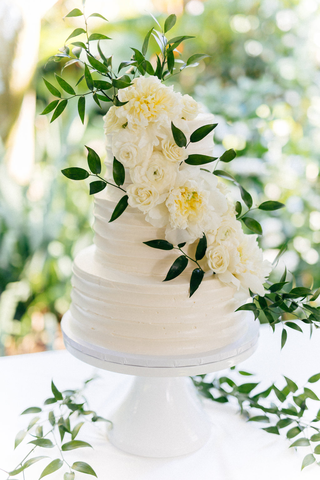 Classic Elegant Three Tier White Wedding Cake Garnished with Real Ivory Flowers and Greenery Leaves on White Cake Stand