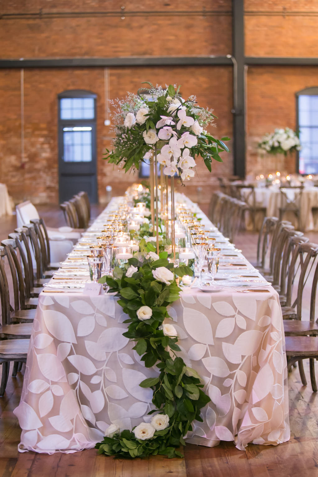 Elegant Modern Romantic Tuscan Inspired Wedding Reception Decor, Long Feasting Table with Floral Linen, Greenery and Ivory Floral Garland, Tall Gold Stand with Ivory White and Greenery Floral Centerpiece | Tampa Bay Wedding Photographer Carrie Wildes Photography | Tampa Bay Wedding and Event Rentals by Kate Ryan Event Rentals | Industrial Tampa Wedding Venue Armature Works | Over The Top Linens