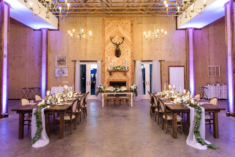 Rustic Country Chic Wedding Indoor Reception Decor, Purple Uplighting Long Wooden Feasting Table, White Table Runner with Greenery Garland, Candlesticks and White Floral Centerpieces, Deer Head Mounted on Wall, White Sweetheart Table | Tampa Bay Wedding Planner Parties A'La Carte | Tampa Wedding Florist Bruce Wayne Florals | Dade City Wedding Venue Covington Farms