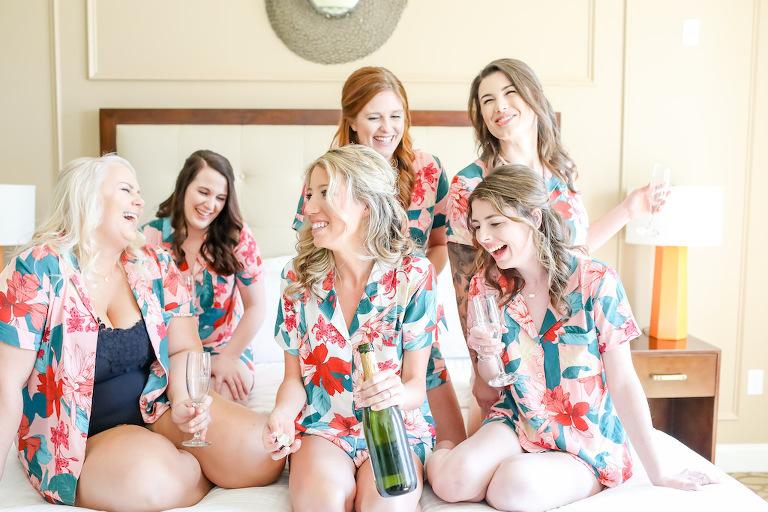 Florida Bride and Bridesmaids Getting Ready Group Photo on Bed, Popping Champagne, Blush Pink Tropical Print Matching Shirts | Tampa Bay Wedding Hair and Makeup Artist Michele Renee The Studio | Tampa Bay Wedding Photographer Lifelong Photography Studios | St. Pete Beach Wedding Venue Hotel Zamora