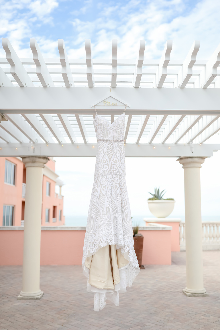 Spaghetti Strap Lace Fitted V Neckline Wedding Dress with Rhinestone Belt on Custom Hanger Outside Pergola of Waterfront Rooftop Hotel Wedding Venue Hyatt Regency Clearwater Beach | Tampa Bay Wedding Photographer Lifelong Photography Studios