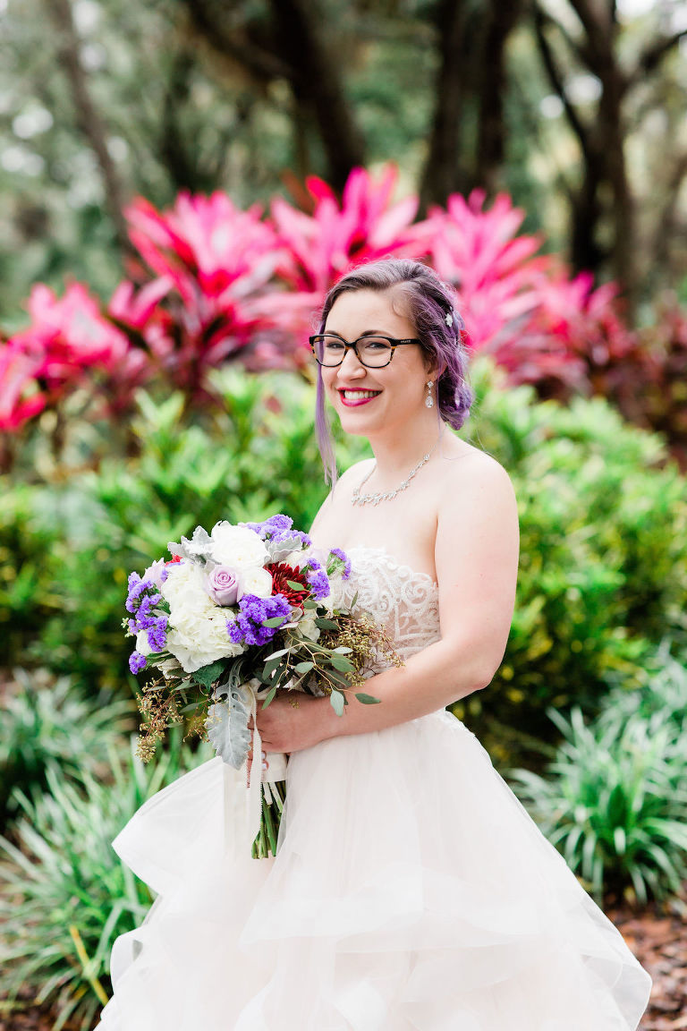 Modern, Romantic Florida Bride in Ballgown Wedding Dress, Unique Wedding Style with Purple Hair and Glasses, Holding Whimsical Bridal Bouquet, Purple, Ivory, White, Red, Flowers with Greenery